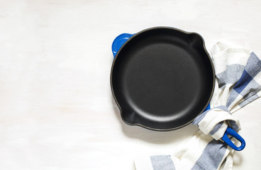 Blue empty cast iron frying pan on white background, top view