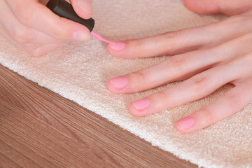 Woman puts first coat of pink shellac on her nails. Close-up hands