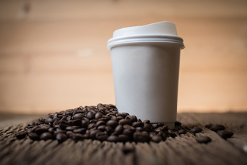Paper coffee cup with coffee bean on the wooden table