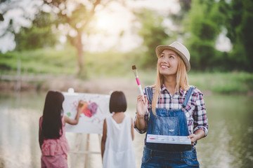 Mother and daughter drawing picture together in the park