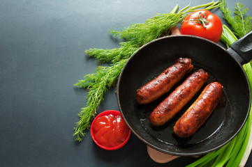 fried sausages on pan with tomato sauce and greens on black