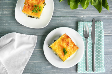 Plates with tasty spinach lasagna on wooden table