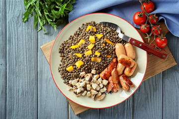 Plate with black lentils, sausages and vegetables on wooden board