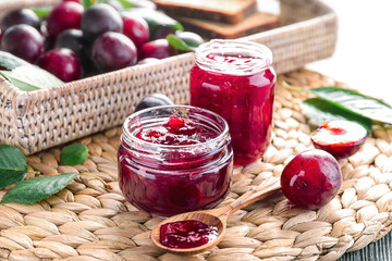 Small glass jars with tasty homemade plum jam on wicker mat