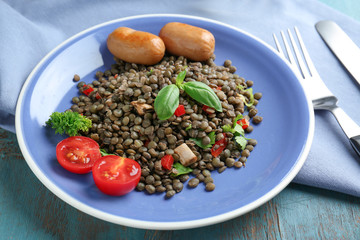 Plate with delicious lentil, sausages and vegetables on wooden table