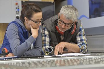 Industrial woodwork technicians reading blueprint
