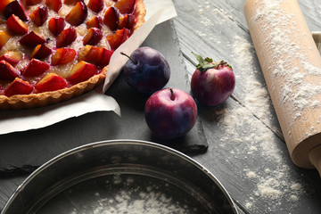 Fresh plums and delicious pie on table