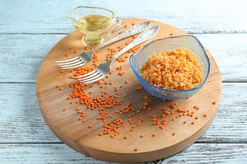 Dish with tasty lentil porridge on wooden board