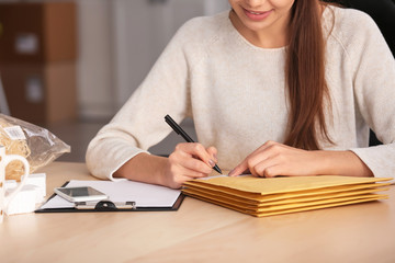 Young woman preparing parcel envelopes for shipment to client in home office