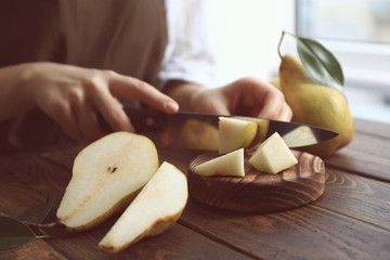 Young woman cutting fresh ripe pear on wooden board