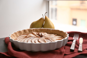 Baking dish with tasty pear tart on table