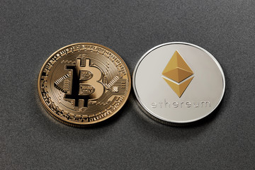 Two coins bitcoin and ethereum on a dark background. Business concept