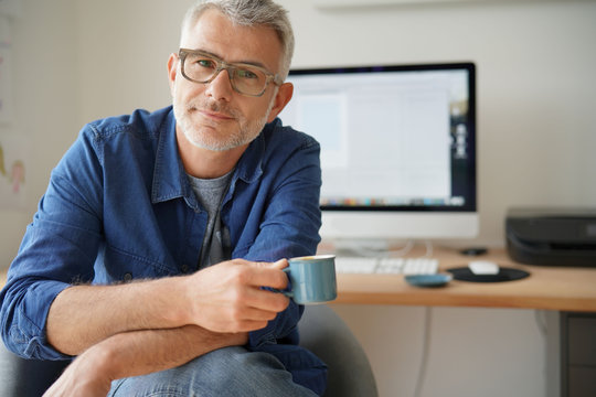Man in home-office drinking coffee