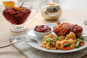 Tasty dish served with cranberry sauce on plate