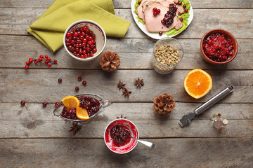 Flat lay composition with tasty cranberry sauce and ingredients on wooden background