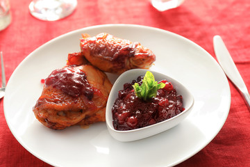 Fried chicken served with cranberry sauce on plate