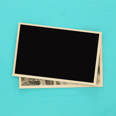 top view of blank photo frames on wooden background.