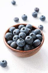 Blueberries in wooden bowl on white background. Closeup view, selective focus