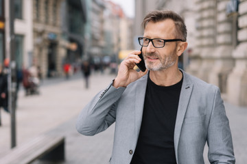 Mature professional man on phone in urban scene