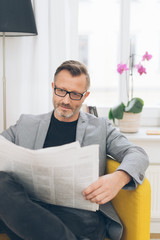 Middle-aged man reading the newspaper at home