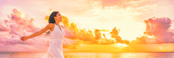 Fototapeten Orange Well being free woman with open arms in the air blissful happiness concept banner. Happy woman against pink pastel colorful sunset sky.