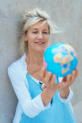 Middle-aged blond woman holding a world globe