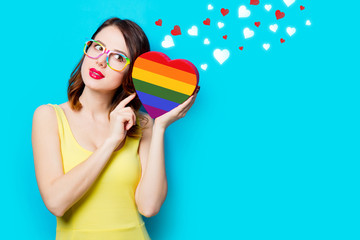 portrait of beautiful young woman with heart shaped box in rainbow color on the wonderful blue studio background with hearts
