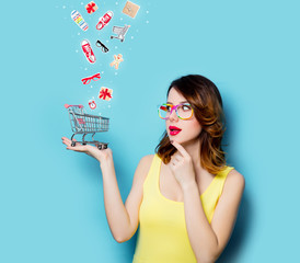 portrait of beautiful young woman with shopping cart on the wonderful blue studio background and with clothes