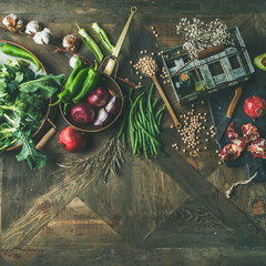 Wall Mural - Winter vegetarian, vegan food cooking ingredients. Flat-lay of seasonal vegetables, fruit, beans, cereals, kitchen utencils, dried flowers, olive oil over wooden background, top view, square crop
