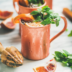 Blood orange Moscow mule alcohol cocktails with fresh mint and ice in copper mugs over white marble background, square crop