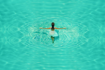 Girl in white dress in blue water pool on a clear sunny afternoon. Creative picture