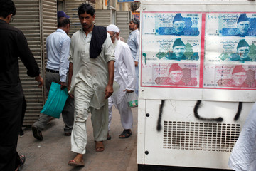 Passersby walk past an advertisement board with photos of Pakistani rupee at a money exchange along a sidewalk in Karachi