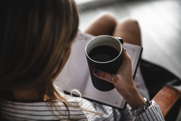Woman on the chair with old book and cup of coffee