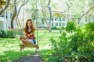 Inspire of happy barefoot girl on swing in sunlight. Carefree woman. Happy attractive trendy young woman laughing as she plays on a swing.