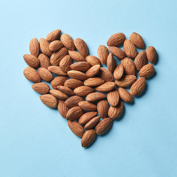 Pattern in the form of heart from almonds on a blue paper background
