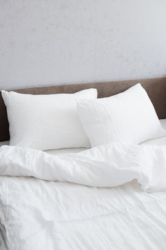 Cozy bed with crumpled white linen