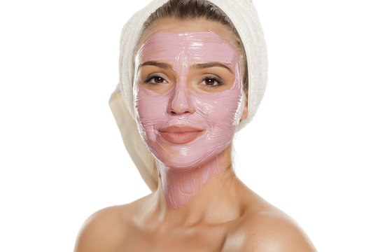 young smiling woman posing facial mask on her face with a towel on her head