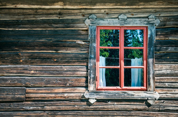 Old and worn timber wall with window at abandoned cottage.