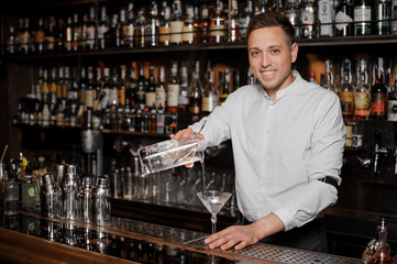 Smiling bartender adding an alcoholic drink into the martini glass