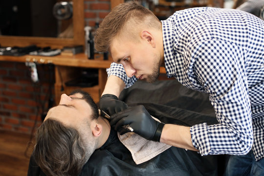 Professional barber working with client in hairdressing salon
