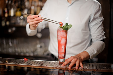 Barman adding the strawberry to the fresh transparent red cocktail with mint leaves