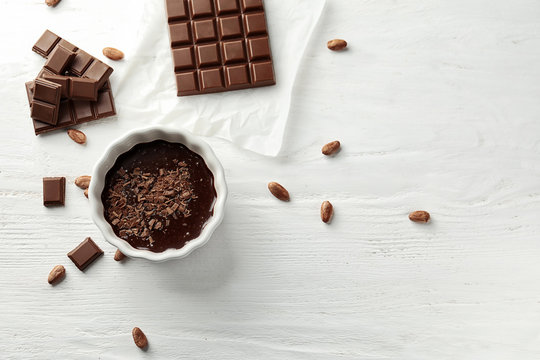 Flat lay composition with delicious chocolate on wooden background
