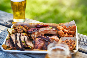 tray of smoked meats texas bbq style outside on picnic table on sunny summer day