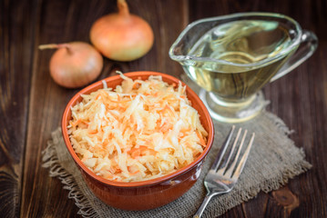 Fresh vegan salad with carrots and cabbage with vegetable oil in a bowl on a dark wood background.