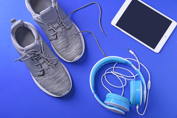 Flat lay composition with sneakers, tablet computer and headphones on color background. Gym workout