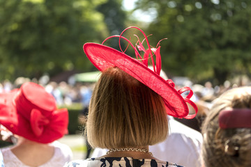 Frau mit rotem Hut auf der Rennbahn in Iffezheim