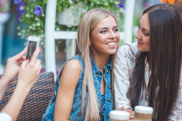 Group of attractive young women making selfie at the cafe and having fun