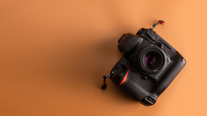 Flat lay, top view of camera on brown background.