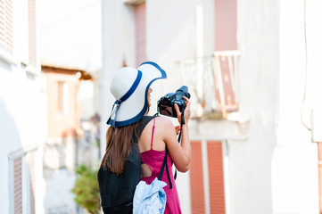 Beautiful young woman tourist with dslr camera taking pictures of beautiful old mediterranean arhitecture in Greece, Europe.