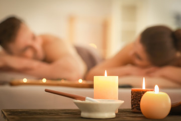 Spa composition with candles and relaxing couple on background